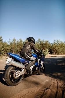 Bella moto su una strada forestale. divertiti a guidare una strada deserta durante un giro in moto sotto i caldi raggi del sole del tramonto.