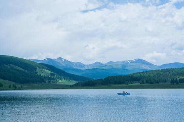 Un bellissimo lago di montagna con canneti circondato da catene montuose e foreste impenetrabili. barca da pesca sul lago.