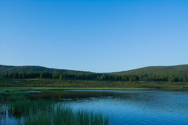Un bellissimo lago di montagna con canneti circondato da catene montuose e foreste impenetrabili.