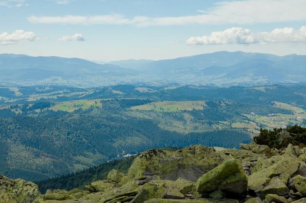 Bellissimo paesaggio di montagna, con cime ricoperte di foreste e un cielo nuvoloso