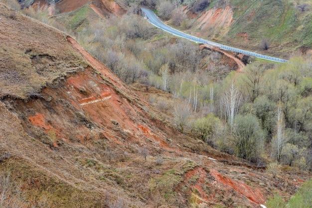 Bella strada di montagna sale. una tortuosa autostrada che si estende in lontananza sullo sfondo di un bellissimo paesaggio primaverile, foreste, montagne, colline e prati. l'inizio della primavera.