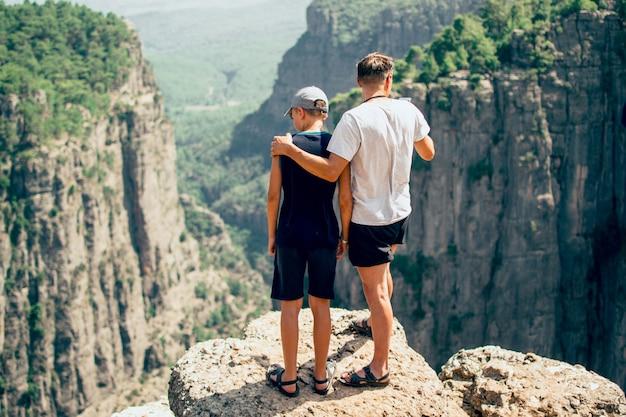 Bella vista sulle montagne padre e figlio in piedi sul bordo