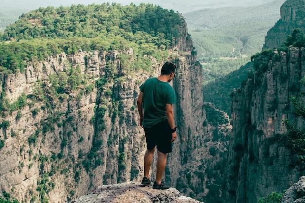 Bellissimo uomo con vista sulle montagne in piedi sul bordo