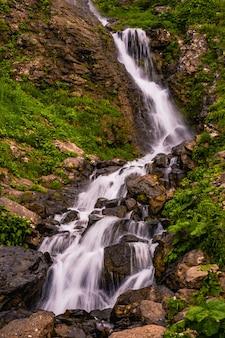Bella cascata di montagna tra gli alberi estate sfondo naturale foto verticale