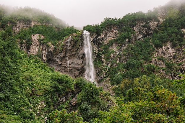 Bella cascata di montagna tra gli alberi estate sfondo naturale