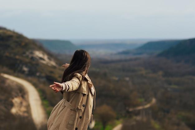 Bellissimo paesaggio di montagne e donna in cima con le mani in alto