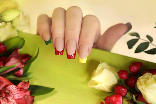 Bella manicure francese multicolore sulla mano di una donna.