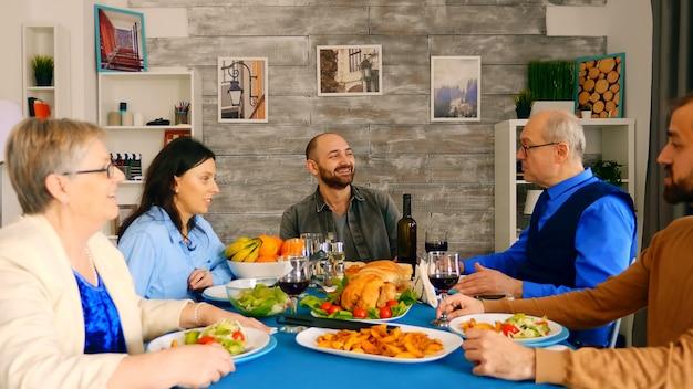 Bella famiglia multigenerazionale che cena insieme a cibo delizioso in una stanza accogliente e luminosa