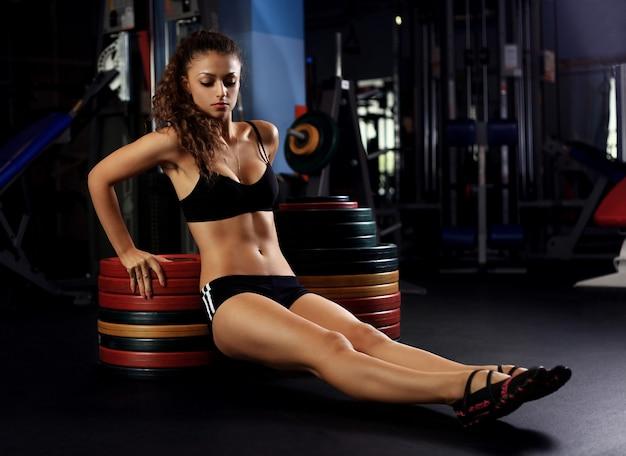 Bella donna in forma muscolare che esercitano i muscoli della costruzione