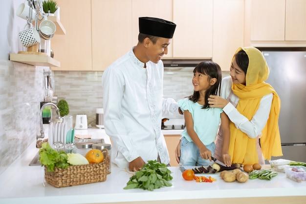Bella famiglia asiatica musulmana che cucina per la cena di iftar insieme a casa. coppia con bambino che si diverte a fare il cibo in cucina
