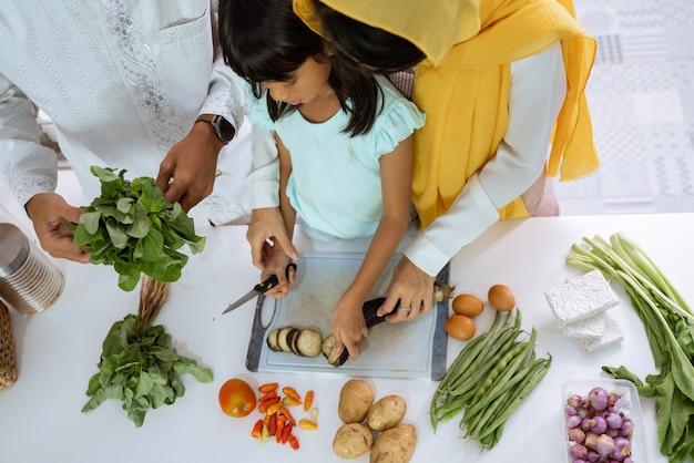 Bella famiglia asiatica musulmana che cucina insieme per la cena iftar a casa. coppia con bambino si diverte a preparare il cibo in cucina