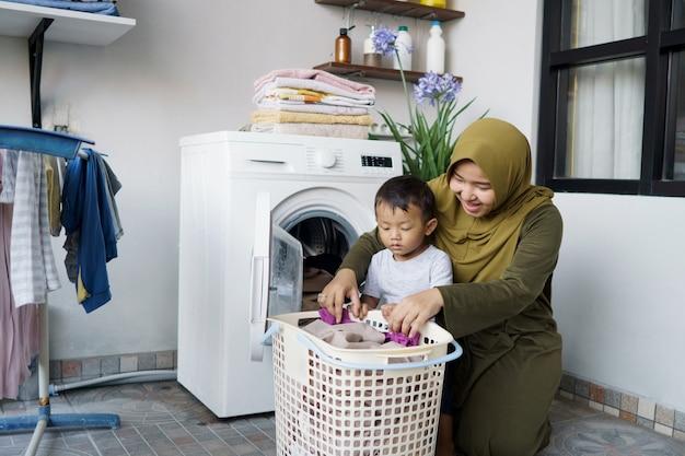 Bella donna asiatica musulmana che fa il bucato con suo figlio insieme