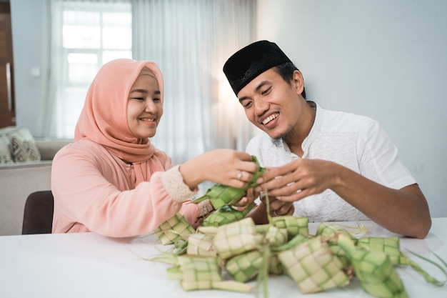 Bella coppia musulmana asiatica rendendo la torta di riso ketupat a casa utilizzando foglia di palma