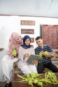 Bella famiglia musulmana e amico che fanno la torta di riso ketupat a casa usando foglie di palma per la tradizione eid fitr mubarak