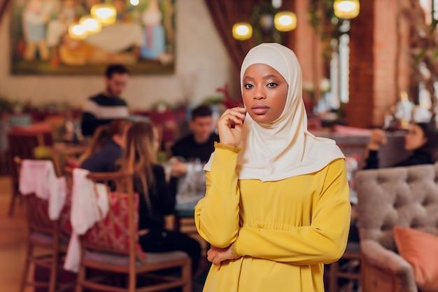 Bella ragazza musulmana in hijab sorridente, aspettando il suo cibo in un ristorante.