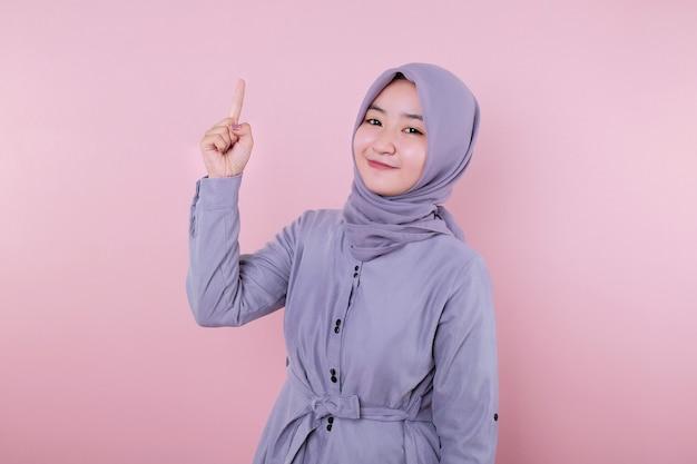 Bella musulmana ha alzato un dito indice con uno sfondo rosa tenue