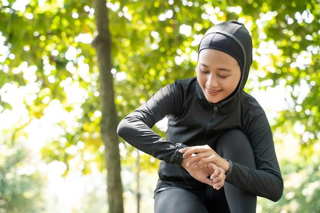 Bella donna musulmana che monitora la sua frequenza cardiaca sull'orologio intelligente durante l'allenamento all'aperto