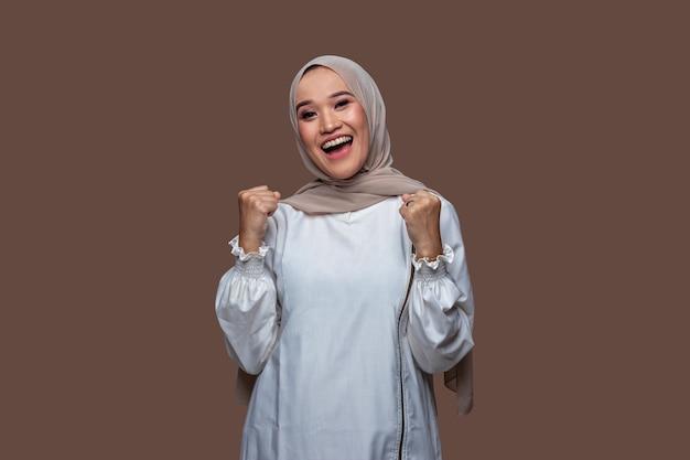 Bella donna musulmana in posa per celebrare il successo alzando le mani