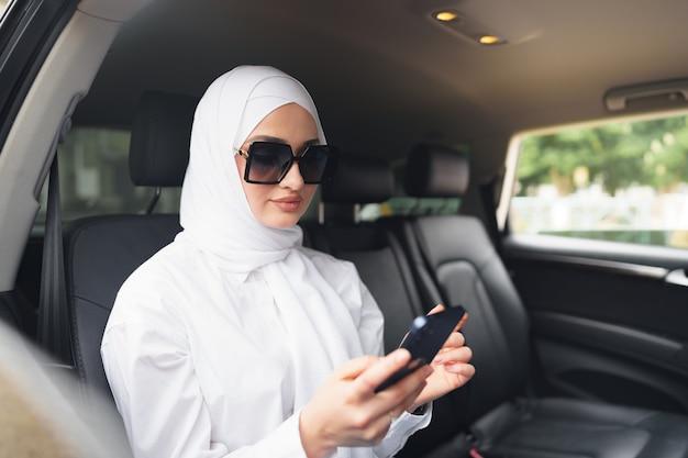 Bella donna musulmana che indossa l'hijab bianco seduta sul sedile posteriore di un'auto e utilizza lo smartphone