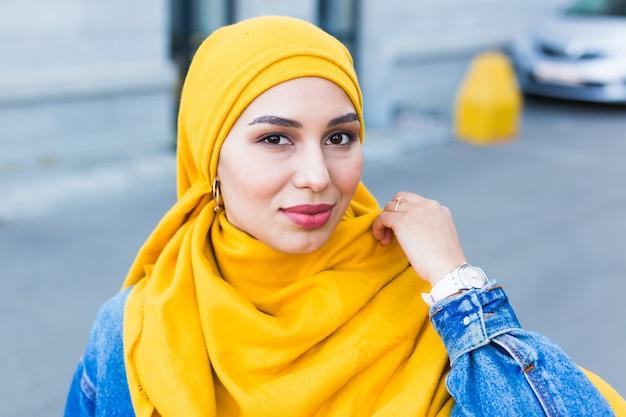 Bella donna musulmana che indossa l'hijab giallo, ritratto di volto femminile alla moda sulla strada della città