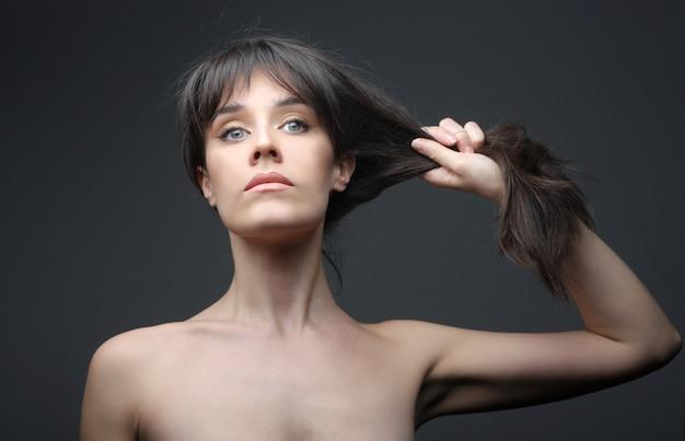 Bella donna nuda tirando i capelli