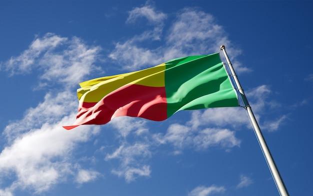 Bella bandiera nazionale dello stato del benin che fluttua al cielo