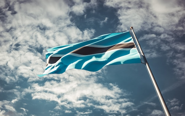 Bella bandiera nazionale dello stato del botswana che fluttua al fondo del cielo.