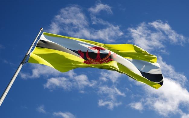 Bella bandiera nazionale dello stato del brunei che fluttua al fondo del cielo.
