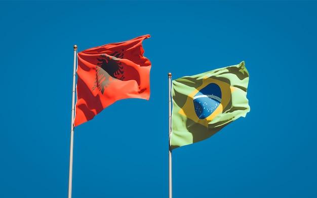 Belle bandiere nazionali dello stato del brasile e dell'albania insieme sul cielo blu