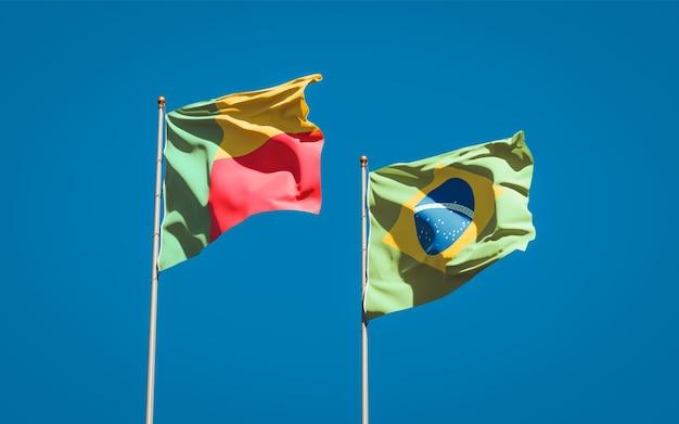 Belle bandiere dello stato nazionale del brasile e del benin insieme sul cielo blu