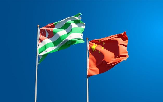 Belle bandiere di stato nazionali della cina e dell'abkhazia insieme al cielo