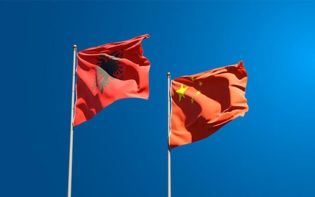 Belle bandiere di stato nazionali di cina e albania insieme al cielo