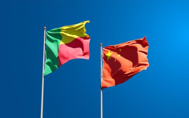 Belle bandiere di stato nazionali della cina e del benin insieme al cielo