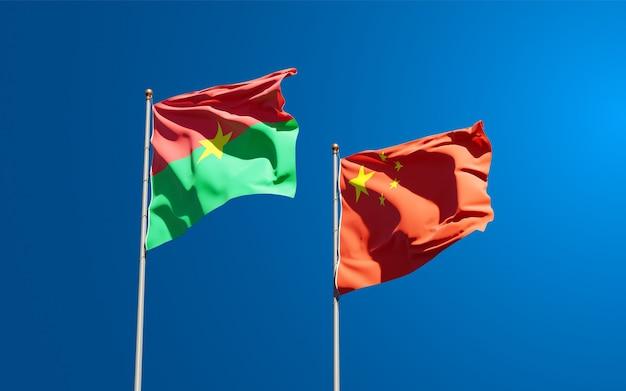 Belle bandiere nazionali di stato della cina e del burkina faso insieme al cielo