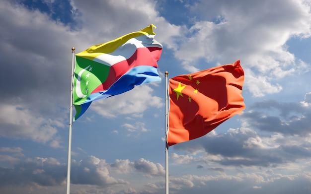 Belle bandiere di stato nazionali della cina e delle comore insieme al cielo