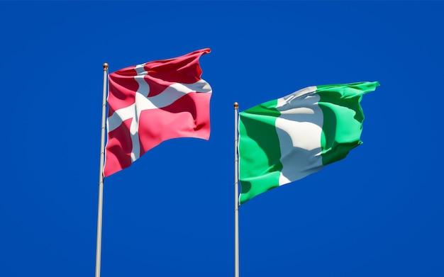Belle bandiere di stato nazionali di danimarca e nigeria insieme sul cielo blu