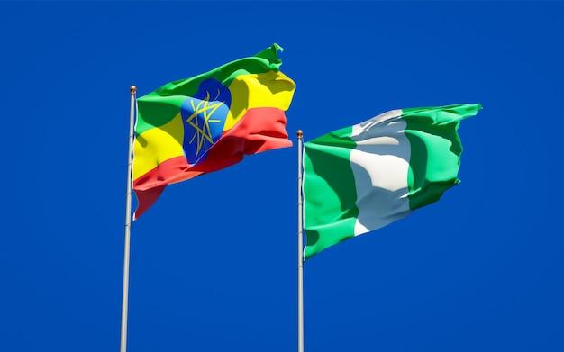 Belle bandiere di stato nazionali dell'etiopia e della nigeria insieme sul cielo blu