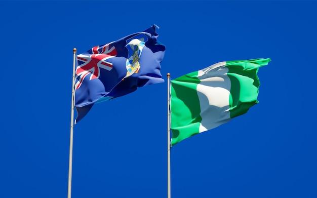 Belle bandiere di stato nazionali delle isole falkland e della nigeria insieme sul cielo blu