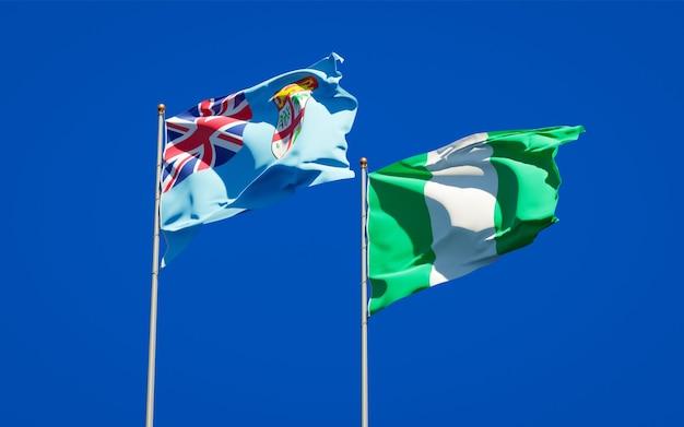 Belle bandiere dello stato nazionale di fiji e nigeria insieme sul cielo blu