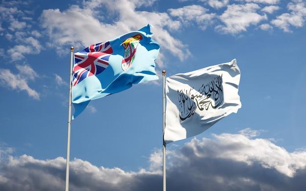 Belle bandiere nazionali di stato delle figi e dei talebani insieme al cielo. concetto di grafica 3d.
