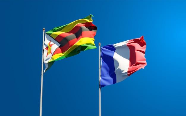 Belle bandiere di stato nazionali di francia e zimbabwe insieme al cielo