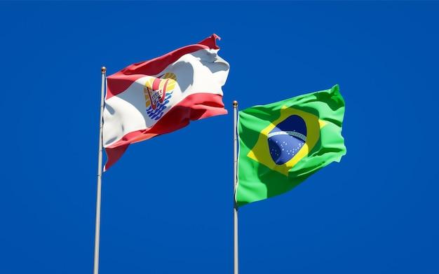 Belle bandiere di stato nazionali della polinesia francese e del brasile insieme sul cielo blu