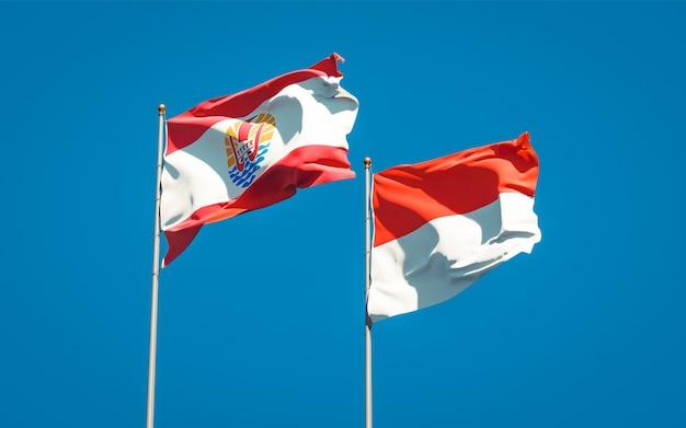 Belle bandiere di stato nazionali della polinesia francese e dell'indonesia insieme sul cielo blu