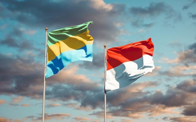 Belle bandiere di stato nazionali del gabon e dell'indonesia insieme sul cielo blu