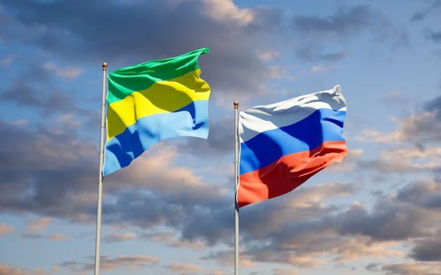 Belle bandiere nazionali dello stato del gabon e della russia insieme sul cielo blu. grafica 3d