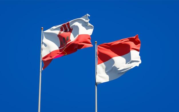 Belle bandiere dello stato nazionale di gibilterra e indonesia insieme sul cielo blu