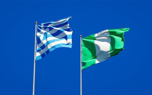 Belle bandiere di stato nazionali della grecia e della nigeria insieme sul cielo blu