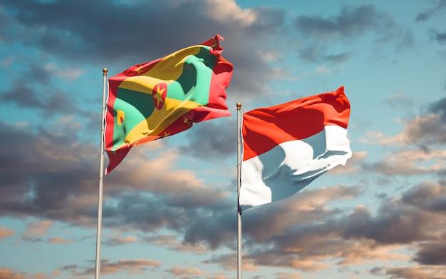 Belle bandiere dello stato nazionale di grenada e indonesia insieme sul cielo blu