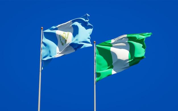 Belle bandiere di stato nazionali del guatemala e della nigeria insieme sul cielo blu
