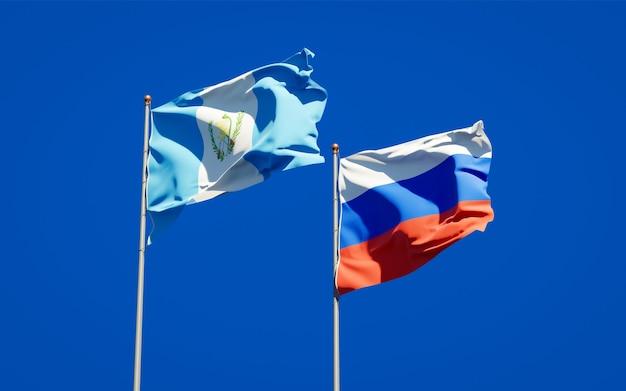 Belle bandiere di stato nazionali del guatemala e della russia insieme sul cielo blu. grafica 3d